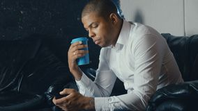 Portrait of busy African American man using a smartphone and drinking coffee in a modern cafe stock video footage