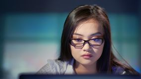 Portrait of busy Asian woman wearing glasses looking at screen of computer working at night