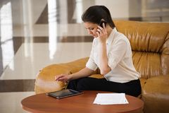 Portrait of busy business woman working on ipad and talking on mobile phone while sitting at sofa. stock photography