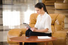Portrait of busy business woman working while sitting at sofa royalty free stock image