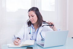 Portrait of busy female doctor at table Royalty Free Stock Photos