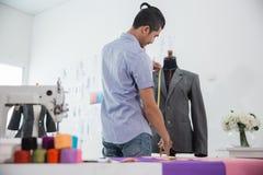 Fashion designer make a suit. Portrait of busy male fashion designer make a suit in his workshop Stock Photo