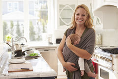 Portrait Of Busy Mother With Baby In Sling At Home Stock Images