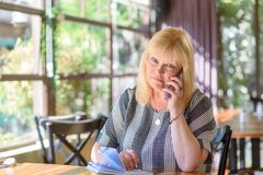 Portrait elegant middle aged plus size businesswoman in office talking on phone. royalty free stock images