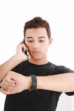 Portrait of a busy young male. Using mobile phone and looking at watch Stock Photo