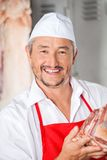 Portrait Of Butcher Holding Meat Royalty Free Stock Photos