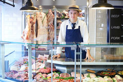 Portrait Of Butcher Standing Behind Counter. Portrait Of Butcher Standing Behind Meat Counter Stock Images