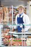 Portrait Of Butcher Standing Behind Counter. Butcher Standing Behind Counter In Shop Royalty Free Stock Image