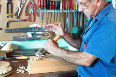 Portrait of cabinetmaker carving a piece of wood with chisel and Stock Image