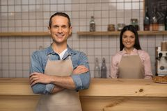 Cafe owner with crossed arms. Portrait of cafe owner with crossed arms standing in coffee shop with waitress on the background Royalty Free Stock Photo
