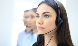 Portrait of call center worker accompanied by her team. Smiling customer support operator at work. Royalty Free Stock Images