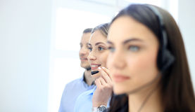 Portrait of call center worker accompanied by her team. Smiling customer support operator at work. Stock Photos