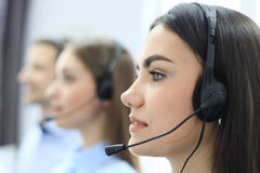 Portrait of call center worker accompanied by her team. Smiling customer support operator at work. Royalty Free Stock Photo