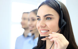 Portrait of call center worker accompanied by her team. Smiling customer support operator at work. Stock Image