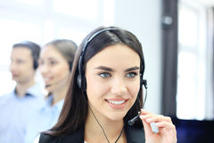 Portrait of call center worker accompanied by her team. Smiling customer support operator at work. Portrait of call center worker accompanied by her team royalty free stock photography