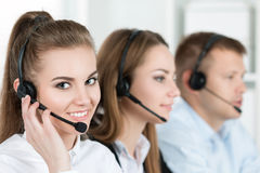 Portrait of call center worker accompanied by her team. Smiling customer support operator at work. Help and support concept Stock Image