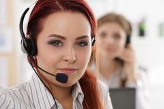 Portrait of call center worker accompanied by her team. Smiling customer support operator at work. Help and support concept stock photo