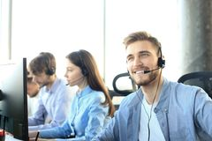 Portrait of call center worker accompanied by his team. Smiling customer support operator at work. Portrait of call center worker accompanied by his team royalty free stock image