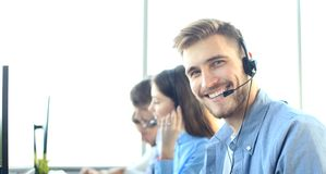 Portrait of call center worker accompanied by his team. Smiling customer support operator at work. Portrait of call center worker accompanied by his team royalty free stock images