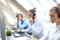 Portrait of call center worker accompanied by his team. Smiling customer support operator at work.  stock photography