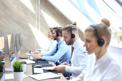 Portrait of call center worker accompanied by his team. Smiling customer support operator at work.  royalty free stock photos