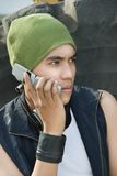 Portrait of calling urban guy. Closeup portrait of young Hispanic urban rapper dude with cap and headphone calling by cellphone against a large worn tire Royalty Free Stock Images