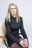 Portrait of Calm Blond Woman Sitting in Light Chair. Studio Shot Stock Photo