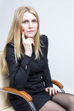 Portrait of Calm Blond Woman Sitting in Light Chair. Studio Shot Royalty Free Stock Image