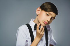 Portrait of calm and mistrust boy isolated on gray background. Normal human emotion, facial expression. Closeup Stock Photography