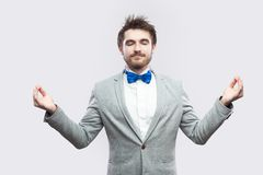 Portrait of calm relax handsome bearded man in casual grey suit and blue bow tie standing with raised arms, closed eyes and doing. Yoga meditating. indoor stock photography