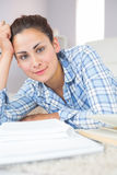 Portrait of calm young student doing assignments while lying on the floor Stock Image