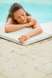 Portrait of calm young woman relaxing in pool Stock Photos