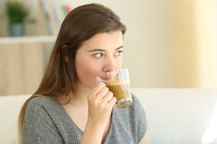 Teen drinking a coffee with milk looking away at home Stock Images