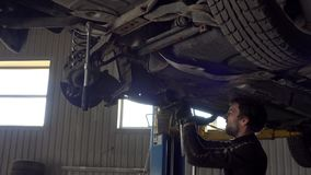 Portrait of car mechanic working with hammer under automobile in auto repair. Service shop stock video