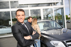 Portrait of car salesman with clients in the back Royalty Free Stock Photos