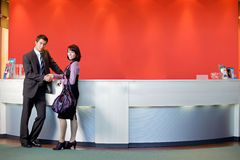 Portrait of car salesman standing with female customer by counter in showroom, shaking hands Royalty Free Stock Image