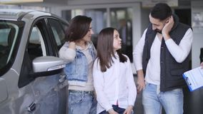 Portrait of car seller talking with young family about of the rule to buy a car in the showroom stock video footage
