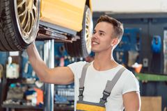 Portrait of a car tuning specialist smiling while checking wheels of tuned car. Portrait of a car tuning specialist smiling, while checking the wheels of a tuned Royalty Free Stock Photos