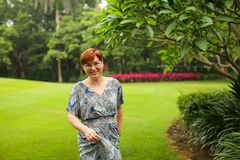Portrait of carefree adult caucasian redhead woman in dress posing in green summer park stock photography
