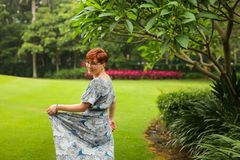Portrait of carefree adult caucasian redhead woman in dress posing in green summer park royalty free stock photos