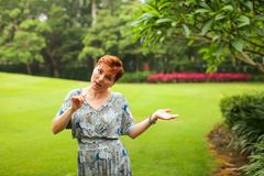 Portrait of carefree adult caucasian redhead woman in dress posing in green summer park royalty free stock images