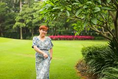 Portrait of carefree adult caucasian redhead woman in dress posing in green summer park stock images