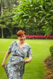 Portrait of carefree adult caucasian redhead woman in dress posing in green summer park royalty free stock image