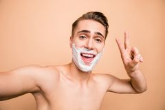Portrait of carefree, careless, rejoice man in foam for shave on. His face looking at camera and make selfie show, give v-sign on beige background royalty free stock photography