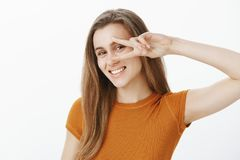 Portrait of carefree happy caucasian woman with blond hair, showing victory or peace gesture with hand over eye, smiling. Joyfully, expressing positive and Royalty Free Stock Photography
