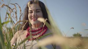Portrait of carefree plump woman in summer dress necklace looking at the camera through the ears of wheat smiling. Portrait of carefree overweight woman in light stock footage