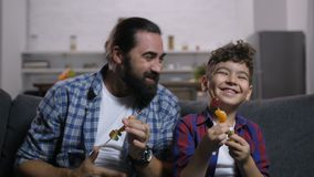 Carefree smiling dad and son enjoying tv show stock video footage