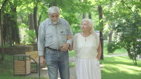 Portrait of carefree senior husband and wife strolling in sunny park and talking. Happy old Caucasian man and woman