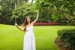 Portrait of carefree young woman in white dress posing in green summer park royalty free stock photography