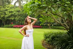 Portrait of carefree young woman in white dress posing in green summer park stock image